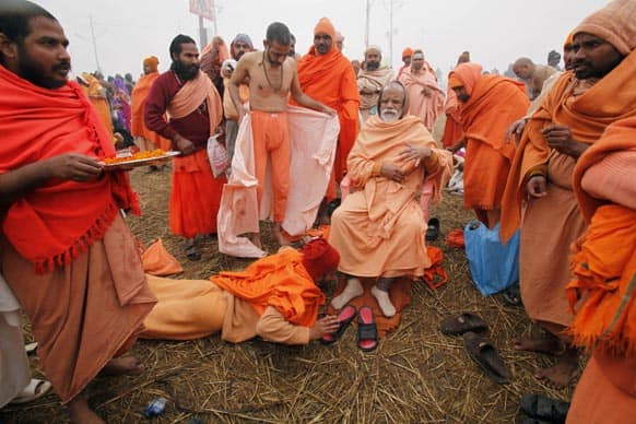 A Hindu holy man, prostrates as he pays respect to a senior holy man at Sangam, the confluence of the rivers Ganges and Yamuna during the Maha Kumbh festival in Allahabad.
