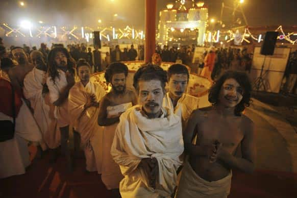 Hindu holy men perform evening prayers at Sangam, the confluence of the Ganges, and Yamuna during the Maha Kumbh Mela, in Allahabad.