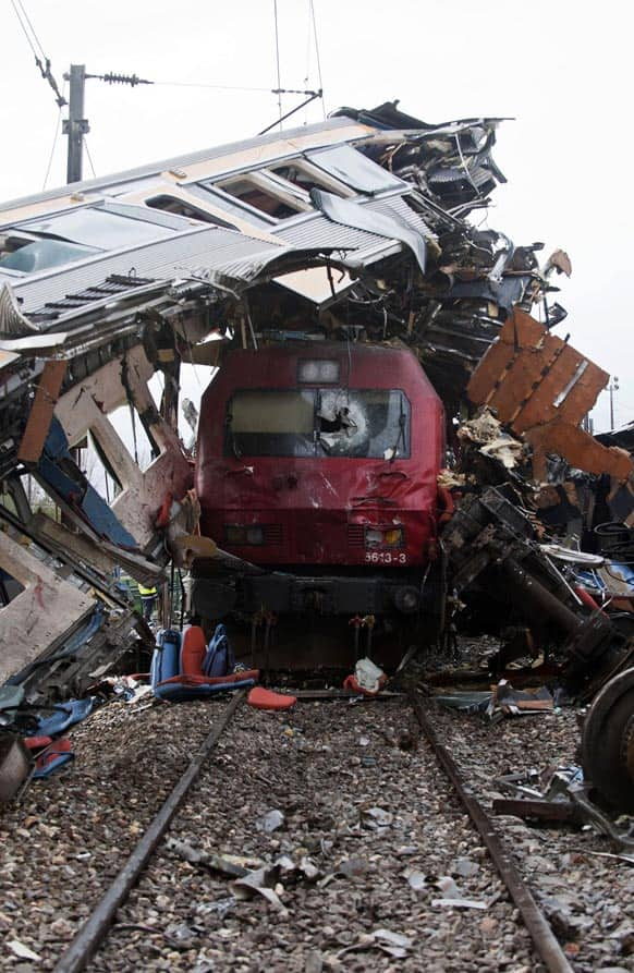 A train sits beneath the carriage of another train after a train crash at a station in Alfarelos, Portugal.