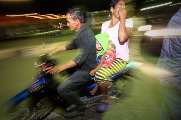 People on motorcycles flee after a strong earthquake hit in Aceh, Indonesia. A strong, shallow earthquake rocked parts of western Indonesia early Tuesday, killing a 9-year-old girl, panicking residents and ruining homes. Several other people were injured.