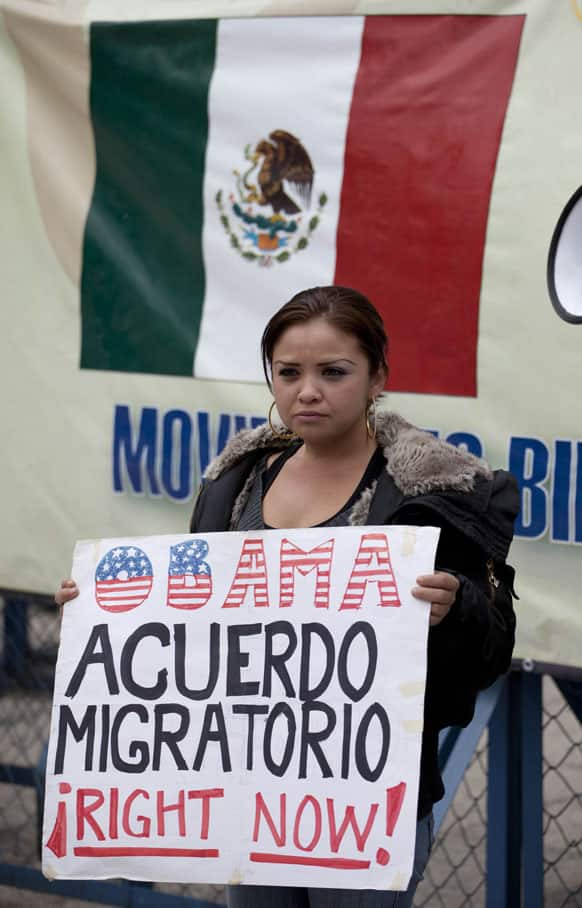 A migrants` rights activist holds a sign that reads in Spanish