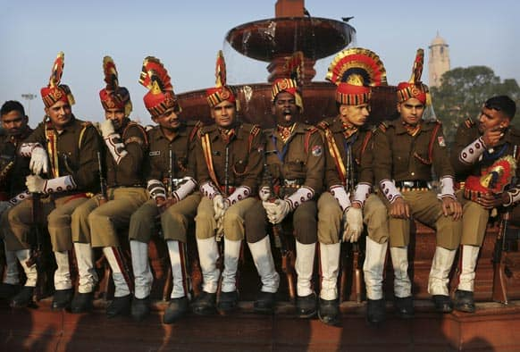An Indian soldier yawns, center, as he and others take a break during preparations for the upcoming Republic Day parade, near the Presidential Palace in New Delhi.