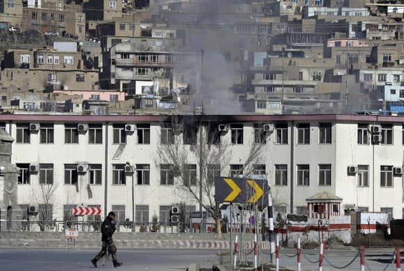 An Afghan security officers takes position, as smoke rises from the building of the Kabul traffic police headquarters in Kabul, Afghanistan.