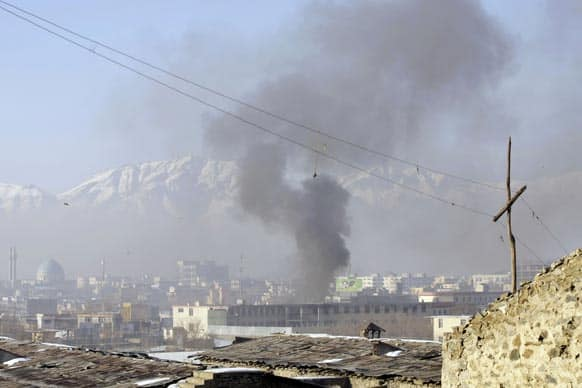 Smoke rises from the building of Kabul traffic police headquarters during insurgents` attack, in Kabul, Afghanistan. Taliban insurgents wearing suicide vests attacked the headquarters before dawn Monday, police said.