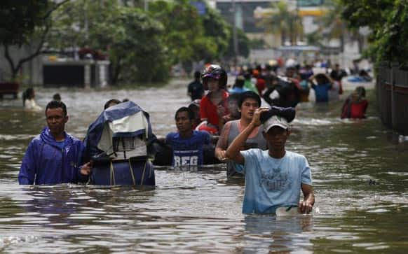 People wade through a flooded street in Jakarta. The death toll from floods in Indonesia`s capital has climbed to 14 after searchers pulled three more bodies from the waters.
