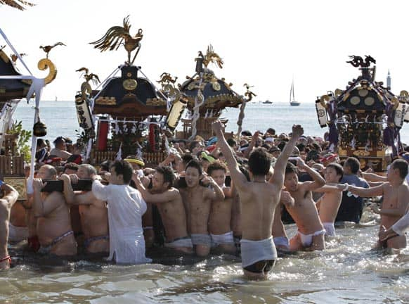 Participants carry a portable shrine and parade through the sea during a mid-winter festival at Enoshima beach in Fujisawa, west of Tokyo.