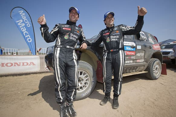 Orlando Terranova of Argentina, left, and Paulo Fiuza of Portugal, right, pose in front of their BMW at the end of 2013 Dakar Rally in in the last 14th stage from La Serena to Santiago, Chile.