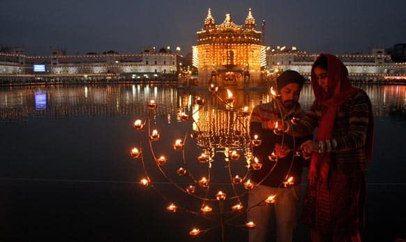 A Sikh couple lights lamps in the grounds of the Golden Temple, Sikh`s holiest temple, illuminated to celebrate the birth anniversary of Guru Gobind Singh in Amritsar.