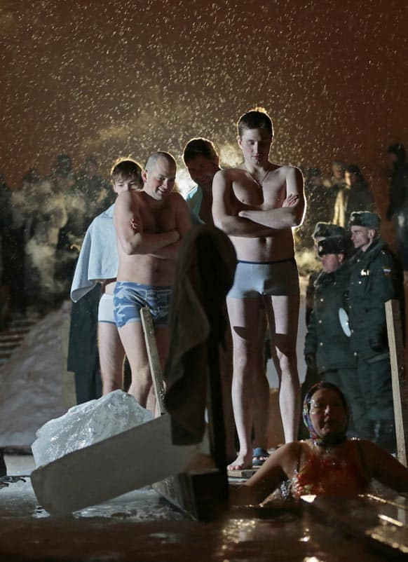 People stand in a queue to the bath of the ice cold water as they take the bath in the ice hole of the pound in the Kolomenskoye park on the outskirts of Moscow.