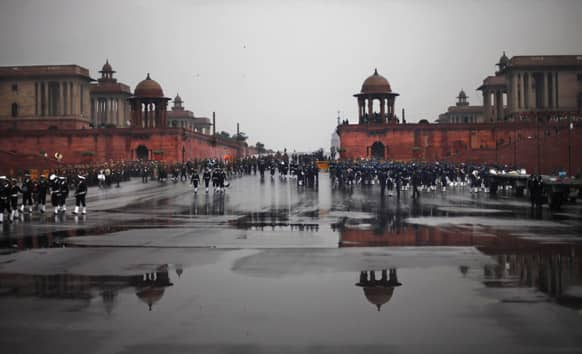 Members of Indian Navy and Air Force walk back to their respective enclosures as rain halts rehearsals for India`s Republic Day parade in New Delhi.