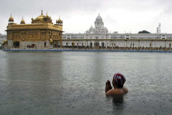 A Sikh devotee pays obeisance as he takes a dip in the holy pond on the birth anniversary of the tenth Sikh guru, Gobind Singh, at Golden Temple in Amritsar.