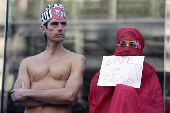 Natalie Mandeau, right, of France, holds up a sign during a demonstration against a nudity ban outside a federal building, in San Francisco.