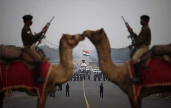Border Security Force personnel sit on camels during preparations for the upcoming Beating Retreat ceremony near the Presidential Palace in New Delhi.