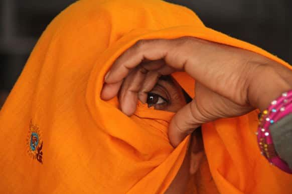An Indian Rajasthani woman peers out from her veil as she waits for a train to return home after attending the Maha Kumbh festival, at a railway station in Allahabad.