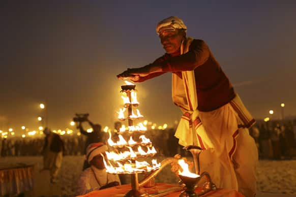 An Indian Hindu priest performs an evening prayer ritual known as Arti, at Sangam, the confluence of the holy rivers Ganges and Yamuna and mythical Saraswati at the Maha Kumbh Mela in Allahabad.
