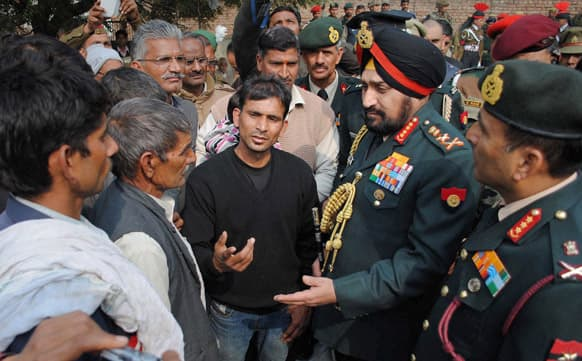 Indian army chief Gen. Bikram Singh speaks with family members of Indian army soldier Lance Naik Hemraj who was allegedly killed by Pakistani soldiers on the Line of Control (LOC), the line that divides Kashmir between India and Pakistan, at Sherpur village.