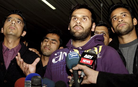 Pakistan hockey player Imran Butt, centre, flanked with other players, talks to reporters at the Lahore airport in Pakistan.