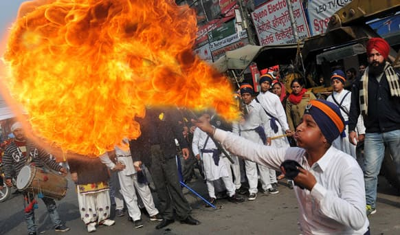 A young Sikh blows flames during a procession to celebrate the birth anniversary of Guru Gobind Singh in Amritsar.