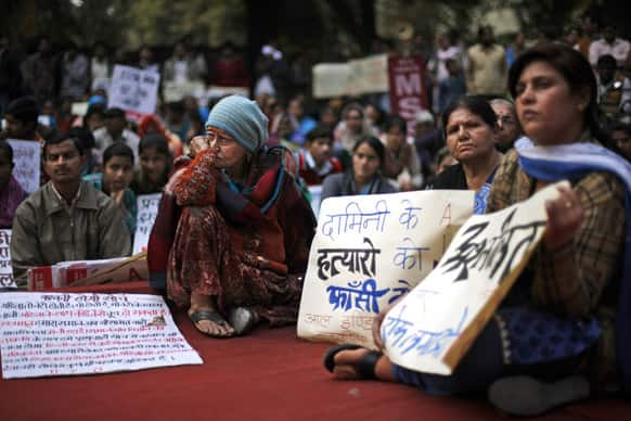 People listen to a speaker during a protest against the alleged inaction by the Indian government in the case of the gang rape of a 23-years old student in a bus a month ago in New Delhi.