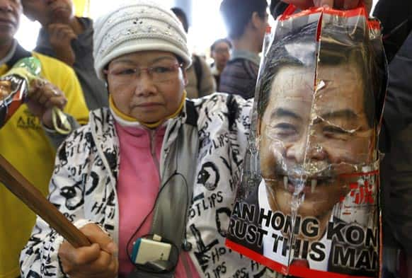 A protester raises a defamed picture of Hong Kong Chief Executive Leung Chun-ying outside the Legislative Council before Leung delivers his policy address in Hong Kong.