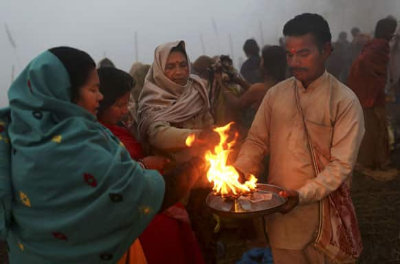 Hindu priest offers blessings to devotees at Sangam, the confluence of the holy rivers Ganges and Yamuna and mythical Saraswati at the Maha Kumbh Mela in Allahabad.