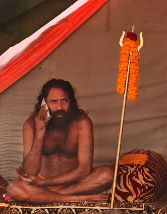 Hindu holy man talks on his mobile outside his camp at Sangam, the confluence of the Rivers Ganges, Yamuna and mythical Saraswati during the Maha Kumbh Mela, in Allahabad.