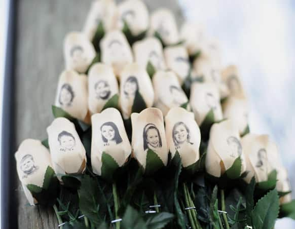 White roses with the faces of victims of the Sandy Hook Elementary School shooting are displayed on a telephone pole near the school on the one-month anniversary of the mass shooting that left 26 dead, including 20 children in Newtown, Conn.