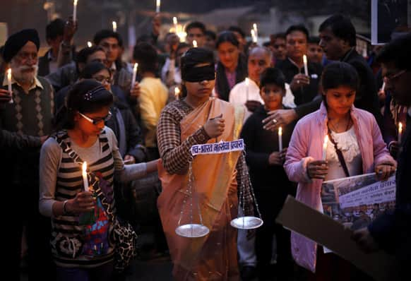 An Indian girl, center, dressed as Lady Justice takes part in a candlelight vigil in New Delhi.