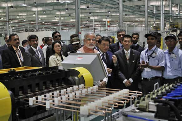 Narendra Modi, CEO of Hitachi Appliances Japan Haruki Yamamoto and MD Motoo Morimoto, watch after the inauguration of the reconstructed manufacturing facility of Hitachi Home and Life Solutions (HHLS), a subsidiary of Hitachi Appliances Inc. Japan, near Kadi, Ahmadabad.