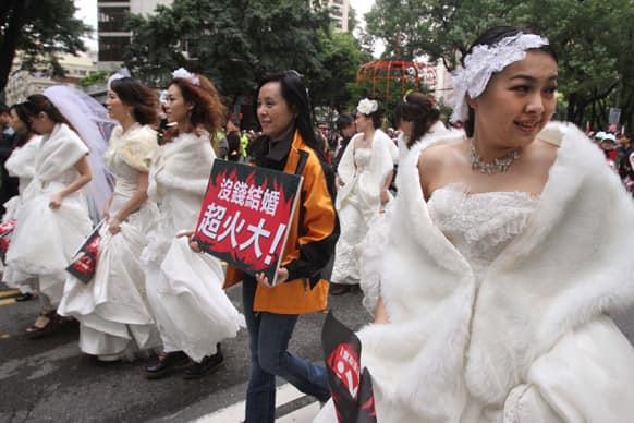 Taiwanese women wear wedding dress and hold slogan reading