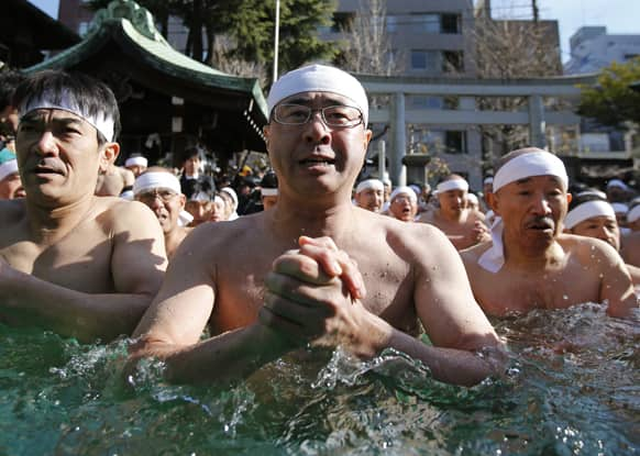 Japanese physical fitness enthusiasts pray while dipping in icy water during a winter ritual to keep themselves fit and display their perseverance at Teppozu Inari Shinto Shrine in Tokyo.