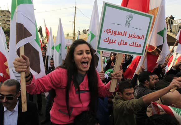 A Lebanese anti-Syrian regime protester holds an Arabic placard that reads,
