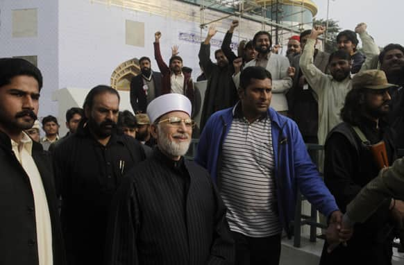 Pakistani cleric Tahir-ul-Qadri, center, surrounded by guards, is greeted by supporters after attending a press conference, in Lahore, Pakistan.