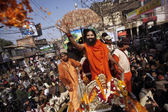 Yoga guru Baba Ramdev throws flower petals to devotees as he participates in a religious procession towards the Sangam, the confluence of rivers Ganges, Yamuna and mythical Saraswati, as part of the Maha Kumbh festival in Allahabad.