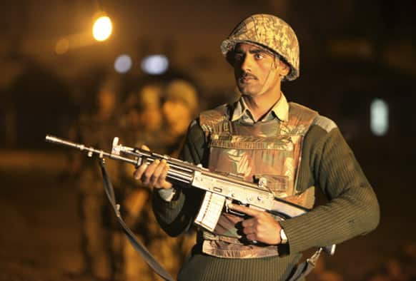 An Indian Border Security Force (BSF) soldier stands guard during a night patrol near international border fencing at Suchet Garh in Ranbir Singh Pura, about 27 kilometers (17 miles) south of Jammu.