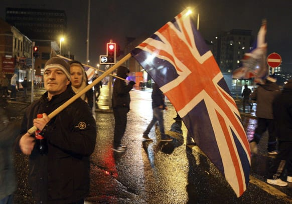 Loyalist protesters hold a British Union flag during clashes with police in the Cloughfern area of Newtownabbey, Belfast, Northern Ireland, during a Union flag protest.