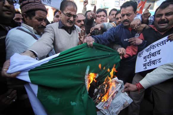 Activists of India's main opposition Bharatiya Janata Party shout slogans and burn a flag of Pakistan during a protest in Jammu.