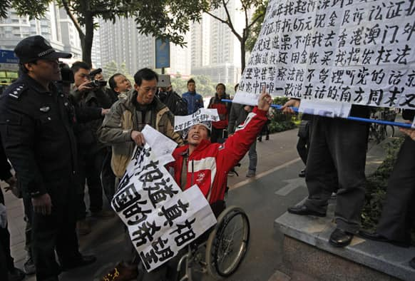 A policeman stands against a supporter in a wheelchair of the Southern Weekly during a protest before being taken away by the police near the Southern Weekly headquarters in Guangzhou.