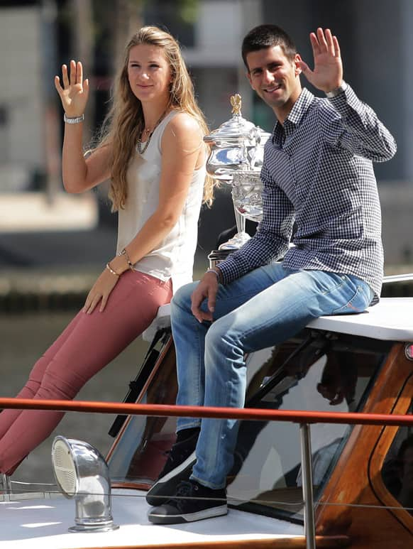Australian Open tennis championship defending women`s singles champion Victoria Azarenka of Belarus, left, and men`s singles defending champion Novak Djokovic of Serbia wave as they arrive with their trophies by boat at the official draw for the 2013 event in Melbourne.