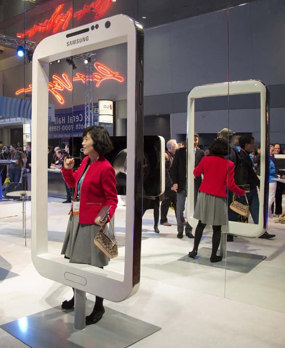 A convention attendee stands in the giant frame of a Samsung mobile device at the Consumer Electronics Show, in Las Vegas.