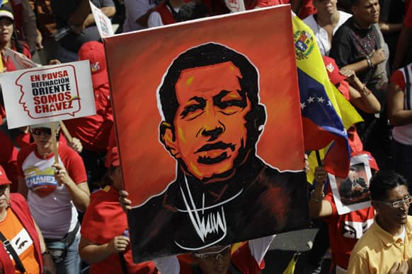 A supporter of Venezuela`s President Hugo Chavez holds up a painting of him during a symbolic inauguration rally for Chavez outside Miraflores presidential palace in Caracas, Venezuela.