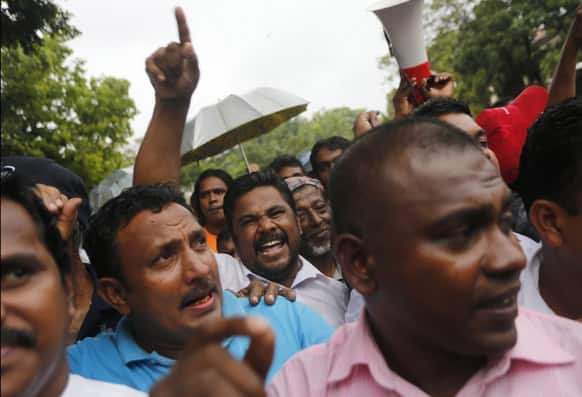 Supporters of Sri Lankan President Mahinda Rajapaksha shout slogans as they block a protest march by Sri Lankan lawyers and opposition groups outside the court complex in Colombo.