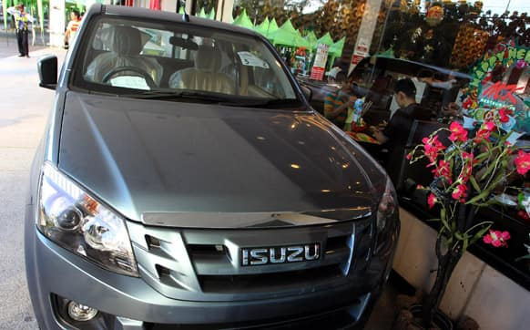 A new Isuzu pickup truck is displayed outside a shopping mall in Bangkok. Isuzu Motors Ltd. and its former shareholder General Motors Co. said Thursday that they plan to jointly develop new pickup truck models, reviving cooperation with an eye to fast-growing emerging markets.