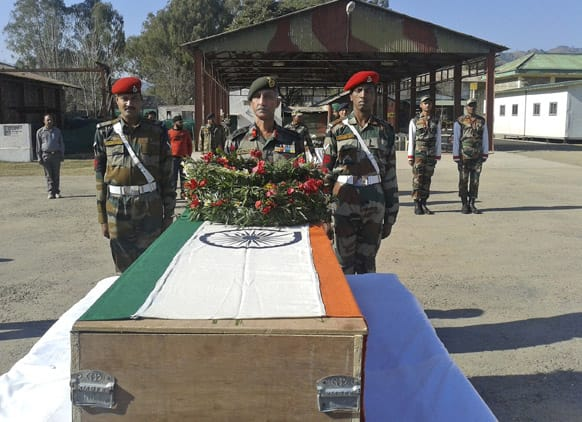 Indian army soldiers offer prayers near the body of a colleague who was allegedly killed by Pakistani soldiers, in Rajouri, India.