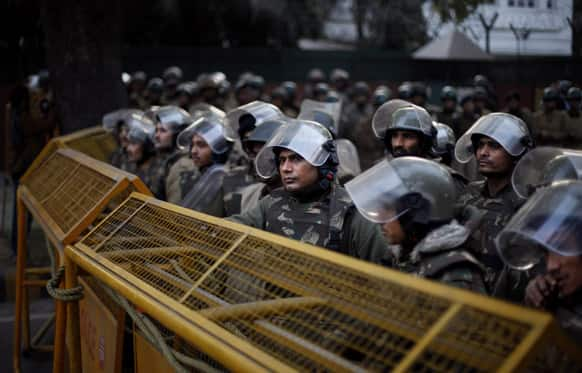 Indian policemen in anti-riot gear stand guard behind police barricades during a protest against Pakistan in New Delhi, India.