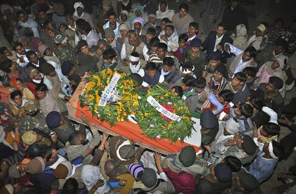 Mourners gather around the body of Indian Army soldier Lance Naik Hamraj who was allegedly killed by Pakistani soldiers on the line-of-control in Kashmir, during his funeral in Mathura district, Utter Pradesh, India.