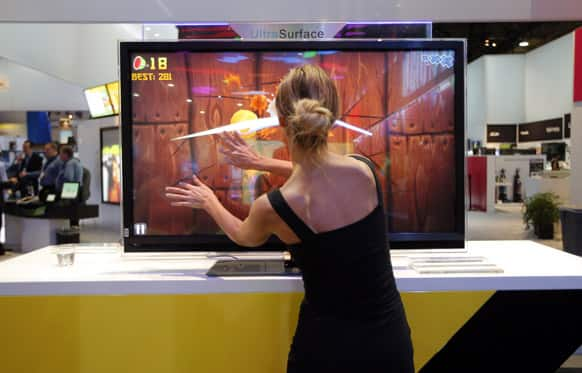 A model plays Fruit Ninja, a popular mobile game, on TCL`s UltraSurface TV at the International Consumer Electronics Show in Las Vegas.