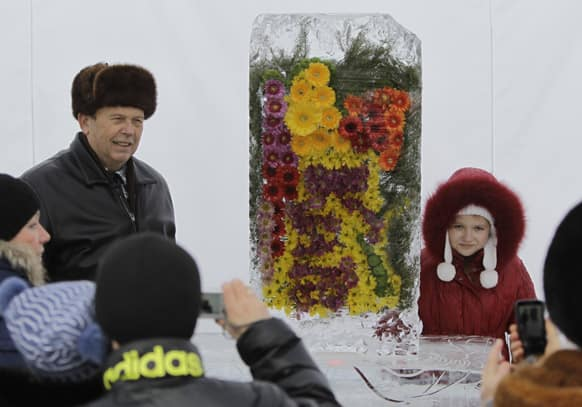 People take pictures near the real ice-covered flowers during the exhibition `Flowers of the Snow Queen` in Kiev, Ukraine.
