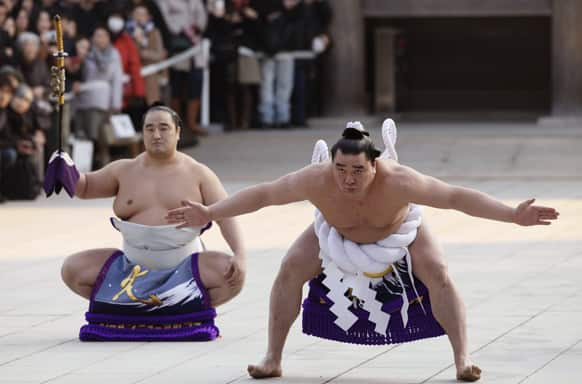 Sumo grand champion or yokozuna Harumafuji , right, from Mongolia, accompanied by sword-bearer Aminishiki , displays the sumo`s ceremonial stamping form during the New Year`s ring entering ceremony by grand champions at Meiji Shrine in Tokyo.