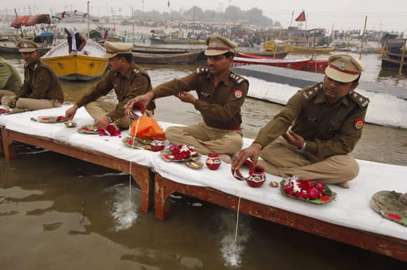 Indian policemen offer prayers to the River Ganges during preparations for the Maha Kumbh festival in Allahabad.